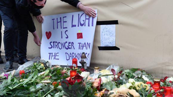 Ein Passant befestigt ein Plakat am Dienstag am Breitscheidplatz. Auch Blumen liegen bereits aus, um den Opfern des vermutlichen Anschlags am Weihnachtsmarkt an der Gedächtniskirche zu gedenken.