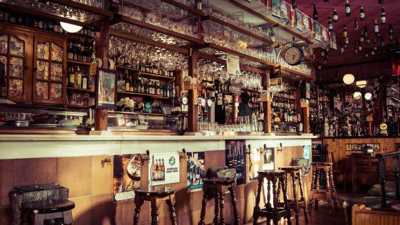 Eine Bar mit rustikalem Tresen mit Barhockern davor sowie mit leeren Bierflaschen als Deko.