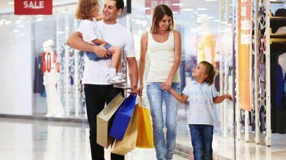 Eine Familie bummelt durch das Einkaufszentrum. Die vollen Taschen zeugen von ersten erfolgen bei der Shopping-Tour.
