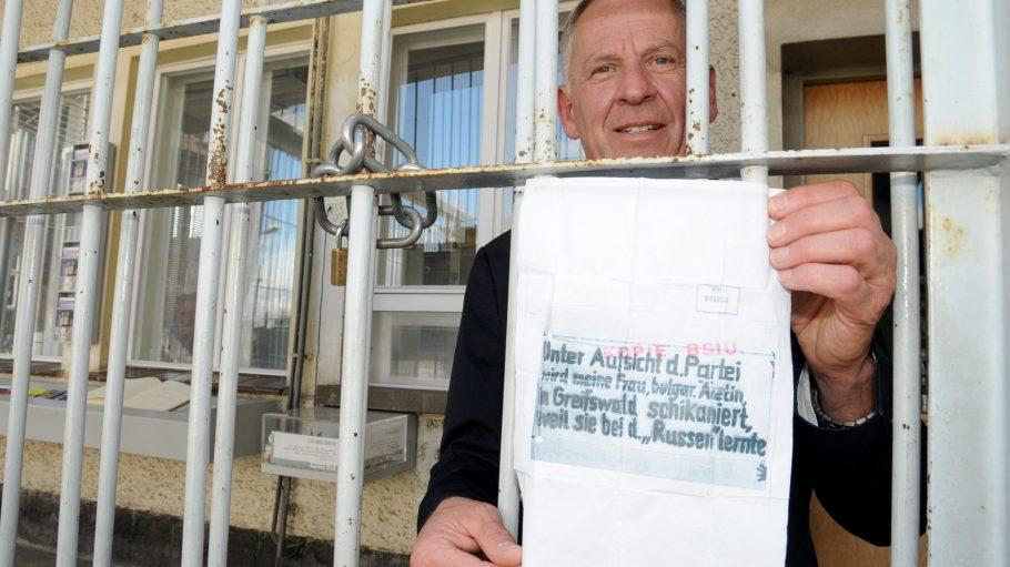"""Ex-Häftling Lothar Schulz mit dem Grund für seine Internierung im """"Stasi-Knast"""": ein kritisches Plakat."""