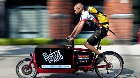Fahrradkurier in Berlin auf einem schwarzen Lastenrad und mit einem gelben Rucksack.