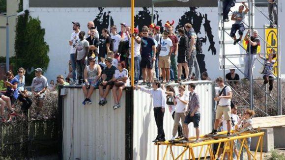 Wo gibt's die beste Sicht? Fans warten auf einem Container stehend auf die Vorbeifahrt der deutschen Nationalmannschaft.