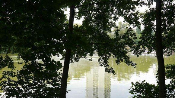 Gegensätze: Ein Hochhaus spiegelt sich im Wasser des Fennpfuhls.