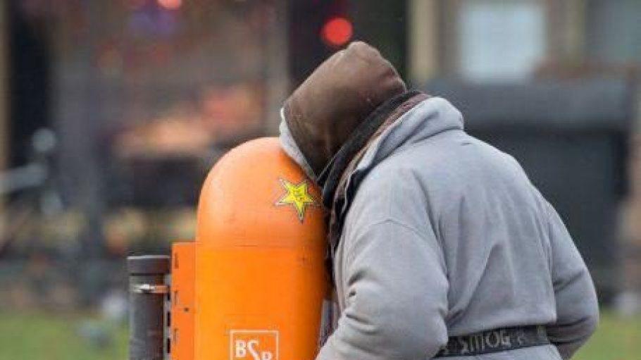 Eine Obdachlose sucht in einem Mülleimer nach Pfandflaschen.