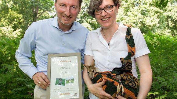 Birgit Monteiro hält ihr Patenkind Monti in dessen Stoffbeutel. Die passende Urkunde bekam die Bürgermeisterin von Tierpark-Direktor Andreas Knieriem überreicht.