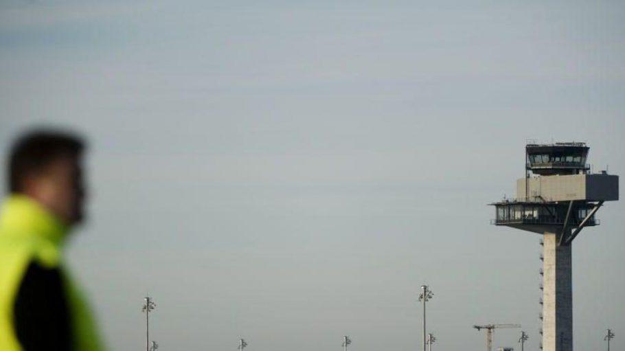 Ein Mitarbeiter steht vor dem BER-Tower des beinahe startklaren Großflughafens Berlin Brandenburg Willy Brandt. Am 3. Juni sollen die ersten Flugzeuge abheben und landen.