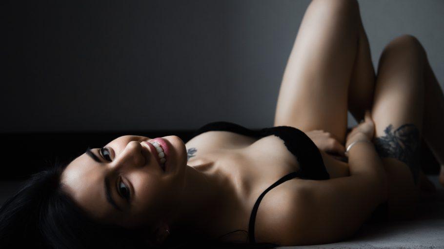Frau in schwarzer Unterwäsche liegt auf dem Rücken, lächeöt in die Kamera und fasst sich an die Innenseiten der Oberschenkel.