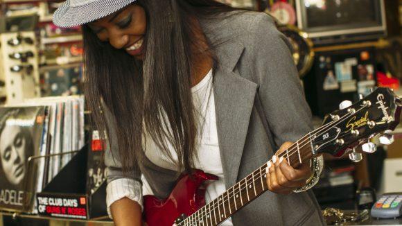 Frau mit Hut und Blazer spielt lachend Gitarre, im Hintergrund sind Schallplatten.