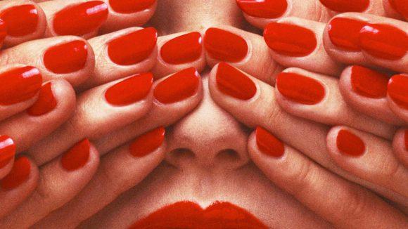 Frau mit roten Lippen werden von mehreren Händen mit roten Fingernägeln die Augen zugehalten.