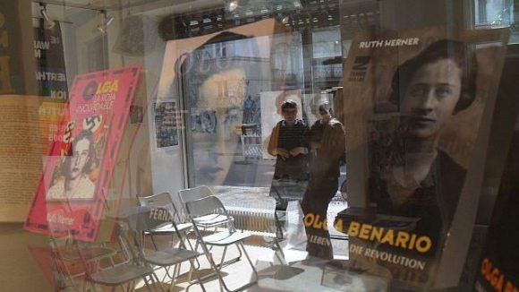 In der Vitrine: Die Olga-Biographie in verschiedenen Sprachen. Gespiegelt werden eine Nachbarin, die sich bei Katinka Krause über wissenschaftliche Literatur zu Olga Benario informiert.