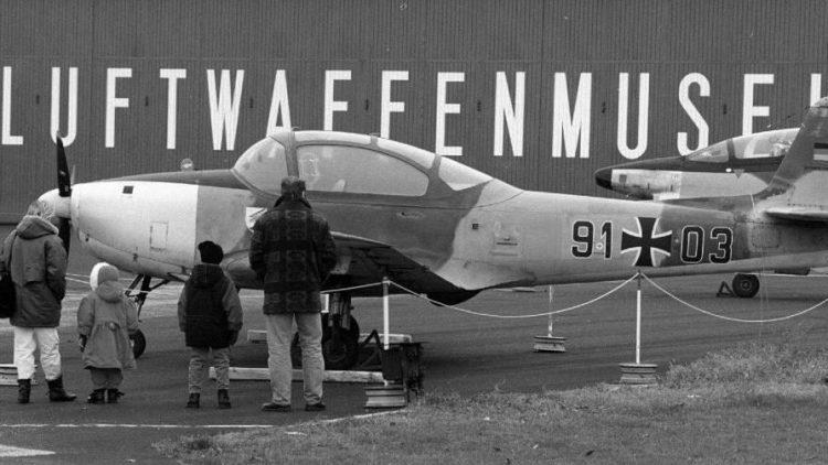Eine Berliner Familie betrachtet auf dem Gelände des Luftwaffenmuseums der Bundeswehr ein zweimotoriges militärisches Aufklärungsflugzeug.