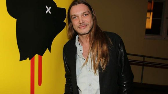 Filmmusiker Philip Eschenbach vor dem eindrücklichen Logo der Genrenale.