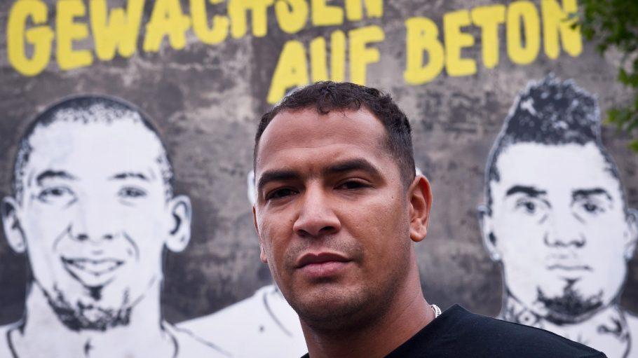George Boateng posiert vor dem Wandbild, auf dem er (verdeckt) mit seinen berühmteren Brüdern Jérôme (l.) und Kevin Prince zu sehen ist.