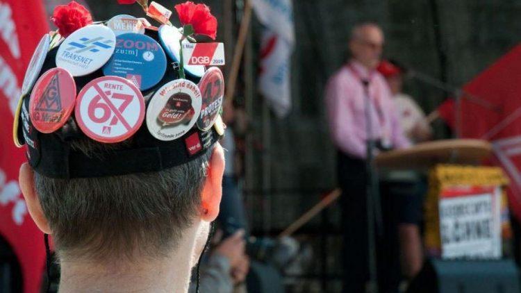 Ein Teilnehmer der traditionellen Demonstration hört sich die Rede des Vorsitzenden der Gewerkschaft Erziehung und Wissenschaft (GEW), Ulrich Thöne, an.