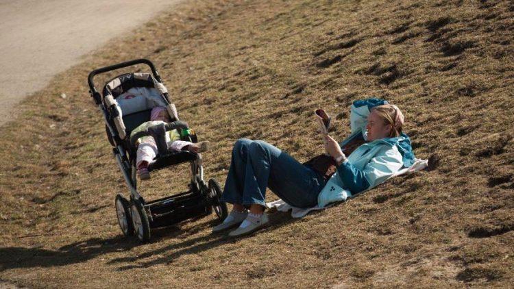 Echte Kreuzberger brauchen keinen Schick: Eine Frau sonnt sich auf einer nicht so grünen Wiesen im Görlitzer Park.