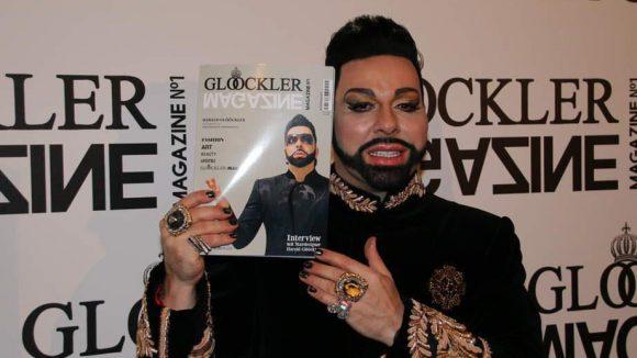 Harald Glööckler - wie immer pompöös gekleidet - hält sein eigenes Magazin in die Kamera. Erst kürzlich veröffentlichte er seine eigene Monopoly-Edition, jetzt legte der Modedesigner nach.