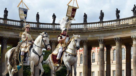 Olympisches Dressurreiten? Na, fast. Wolfgang und Diana Krischke posieren in historischen Kostümen auf ihren Pferden vor den Kolonnaden in Sanssouci. Zur Wiedereröffnung der sanierten Kolonnaden soll vor der historischen Kulisse am 11. September eine barocke Pferdeoper mit 24 Tieren stattfinden - und 2024 vielleicht Olympia.
