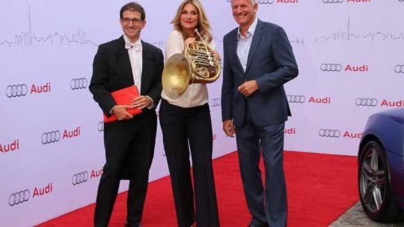 Hornist Arnaud Morel (l.) borgte sein Instrument der Moderatorin Kim Fisher, daneben Audi Vertriebschef Region Ost Alexander Schumacher.