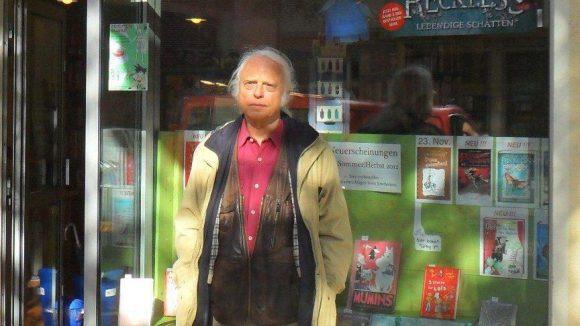 Autor Horst Bosetzky, weiße Haare, helle offene Jacke, steht vor dem Schaufenster eines Buchladens