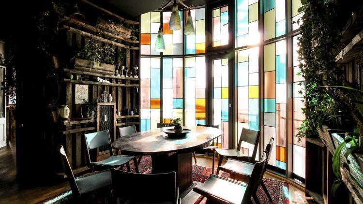 Tisch mit Stühlen auf Teppich vor buntem Fenster im House of Small Wonder