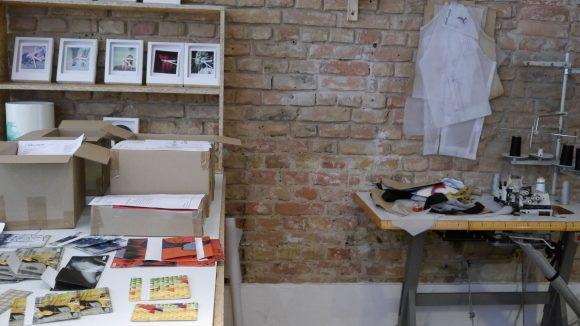 Arbeitsplatz von Marc Aurel Hartung im Atelierladen I like Paper; links oben stehen die Polarorid-Wanduhren.