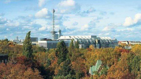 Das ICC, fotografiert von Halensee aus, mit Blick über die Bäume und die Kapelle des Friedhofs Grunewald.