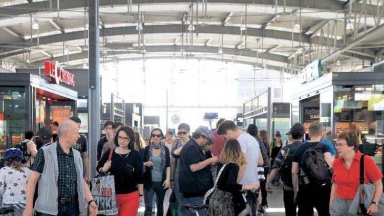 In der Bahnhofshalle am Ostkreuz drängen sich die Menschen zwischen Verkaufsständen und Reklametafeln.