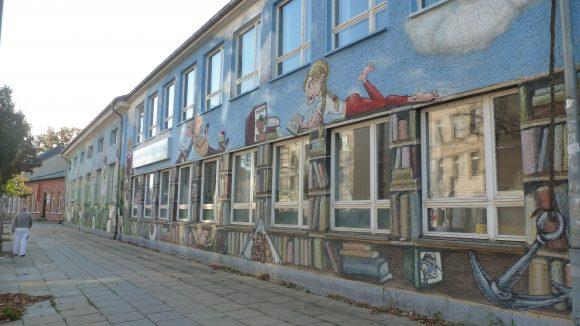 """Die Friedrich-Wolf-Bibliothek - benannt nach dem Schriftsteller, Arzt und kommunistischen Politiker - in der Winckelmannstraße. Die halbstarken Jugendlichen des Ortes sitzen aber eher auf der anderen Straßenseite, sagen Sätze wie """"In der Schule; ich kann dir mit allem aushelfen, ich kann alles besorgen ich schwör's."""""""