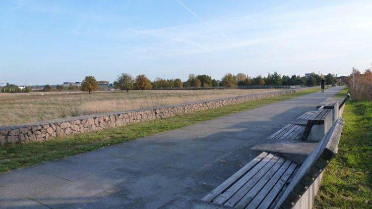 Eine breite, flache Steinmauer signalisiert die Barriere zwischen Naturschutzgebiet und Spazierweg. Immer wieder laden Sitzbänke und Informationstafeln zum Verweilen ein.