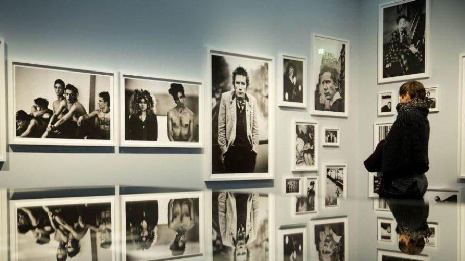 Eine Frau betrachtet Bilder von Johnny Rotten (Sex Pistols) in der Berliner C/O Galerie.