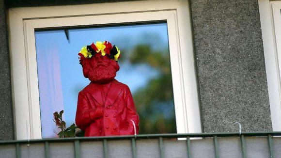 Drollig und draußen. Hier freut sich ein Bewohner mithilfe einer dekorierten Karl-Marx-Figur offensichtlich über Erfolge der deutschen Fußballnationalelf. Fröhliches Singen auf dem Balkon ist in Berlin jetzt vom Ordnungsamt in Friedrichshain untersagt worden.
