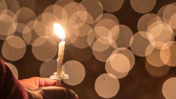 Eine Kerze erhellt die Dunkelheit.