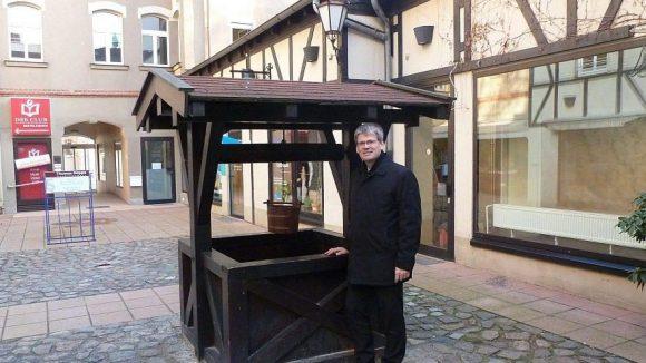 Helmut Kleebank am mittelalterlichen Brunnen in einem Hinterhof an der Breiten Straße.