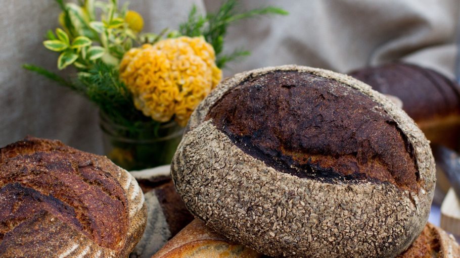 Zwei dunkle Brote und ein Baguette liegen auf einem Tisch, im Hintergrund sind unscharf gelbe Blumen zu sehen