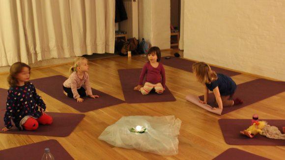 Der Raum in Friedenau ist gemütlich und behaglich. Die Kids sitzen auf ihrer eigenen Matte im Kreis.