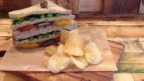 Auf einem Brettchen serviert: Das Clubsandwich mit grünem Spargel auf Olivenpesto mit Mandel-Mayo und Meersalz-Kartoffelchips.