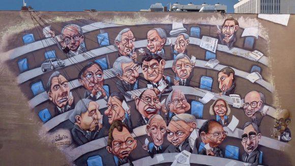Eines der größten Wandgemälde in Berlin zeigt Willy Brandt und Theo Weigel als Marionetten der Wirtschaft.