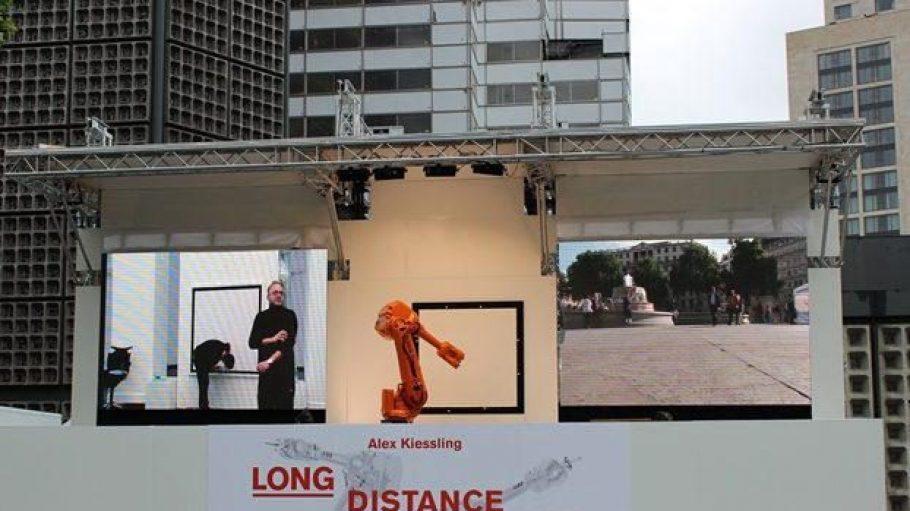 Fünf vor 11: Künstler Alex Kiessling wärmt sich auf. Mittig wartet IRB 4600_1 stoisch am Breitscheidplatz auf Input. Und rechts am Trafalgar Square in London scheint die Herbstsonne.