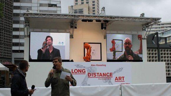 """""""Long Distance Art"""" ist wie ein Open Air Konzert aufgebaut. Große Bühne mit Überdachung, Moderatoren, die per Live-Schaltung aus der jeweiligen Stadt berichten. Hier hapert es übrigens ein bisschen, manchmal fällt der Ton der Moderation in London aus."""