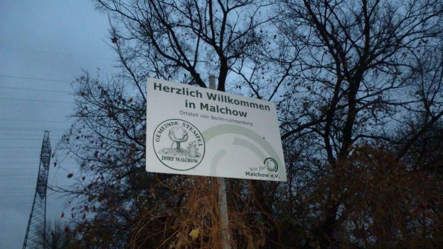 Ortseingang von Malchow in der Dämmerung. Der Strommast im Hintergrund ist nicht der einzige in der Umgebung.