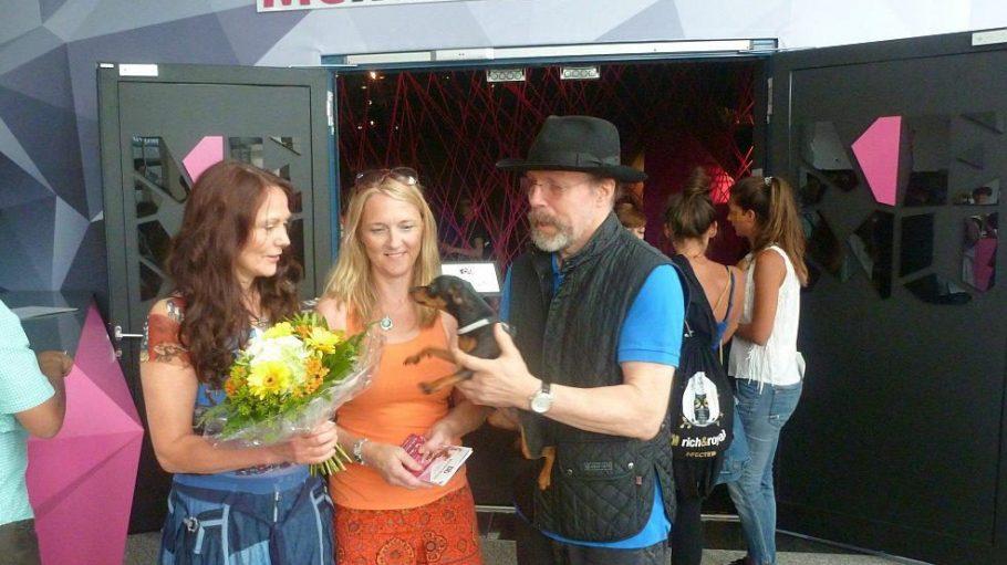 Scheinbar möchte auch der Hund von Dr. Gunther von Hagens der hunderttausendsten Besucherin Inke Kaerkes (Mitte) gratulieren. Kuratorin Angelina Whalley, Ehefrau von von Hagens, überreicht einen Blumenstrauß.