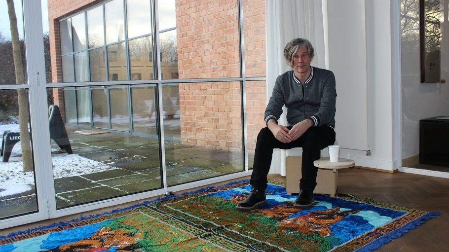Künstler Joerg Waehner hat es sich im Mies van der Rohe Haus gemütlich gemacht. Die schönen Teppiche sind eine Anspielung auf den früheren Nutzer des Gebäudes, das Ministerium für Staatssicherheit.