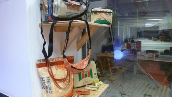 Auch Taschen von Goroya werden im Mount Fair verkauft. Im Hintergrund: Blick in Lager und Werkstatt.