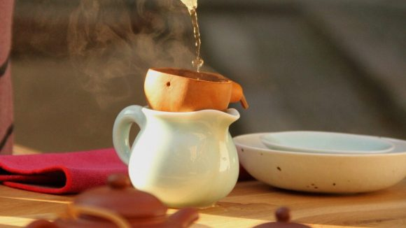 Weiße Teekanne mit tönernem Aufsatz zum Aufgießen, in den gerade von oben Wasser gegossen wird. Im Vordergrund weitere Kannen