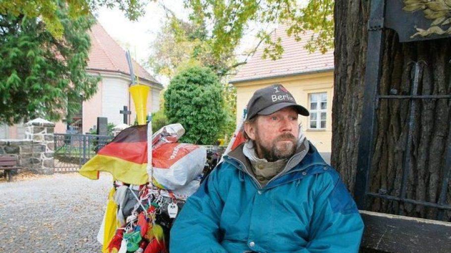 """Peter, ein wohnungsloser Zehlendorfer; in seinem """"Wohnzimmer"""" vor der Dorfkirche, der Friedenseiche und der alten Dorfschule in Zehlendorf-Mitte."""
