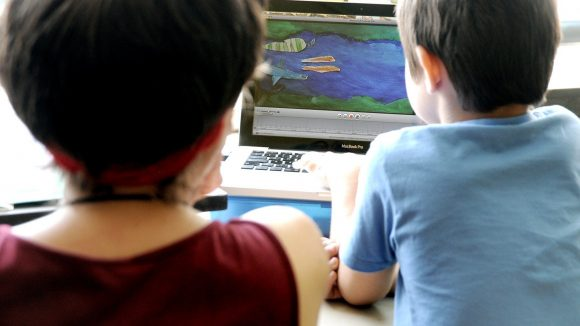 Anzor (r.) drückt auf die Leertaste und löst damit ein Bild aus. Im Rahmen der Filmprojekttage mit dem Papierkino lernen die Kids Schritt für Schritt, wie man Filme macht.