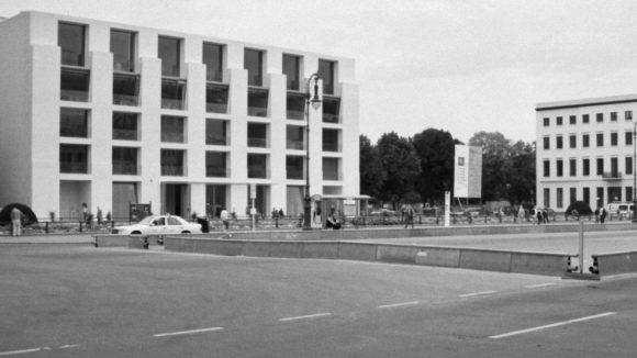 """Pariser Platz in Mitte, 1999. Links die DZ-Bank (früher DG-Bank). Das Gebäude wurde von Frank O. Gehry entworfen, der für seine dekonstruktivistische Architektur bekannt ist. Während das Gebäude im Innern und auf der Rückseite (Behrenstraße) ein """"echter"""" Gehry ist, fällt die Fassade zum Pariser Platz aufgrund der strikten Gestaltungsvorgaben für den Bereich vor dem Brandenburger Tor aufreizend nüchtern aus."""