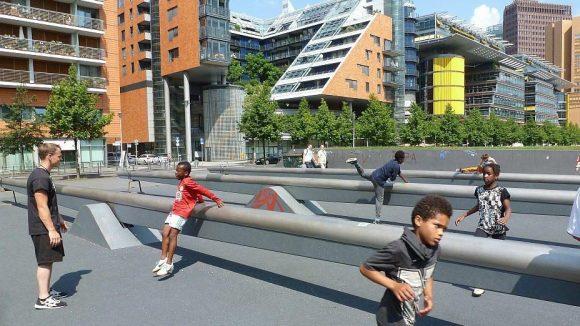 """Unter Anleitung eines Trainers von """"ParkourOne"""" (links im Bild) geht es vor urbaner Kulisse zur Sache."""