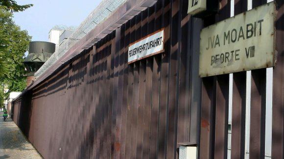 Passanten laufen am Zaun der Justizvollzugsanstalt in Berlin Moabit vorbei.