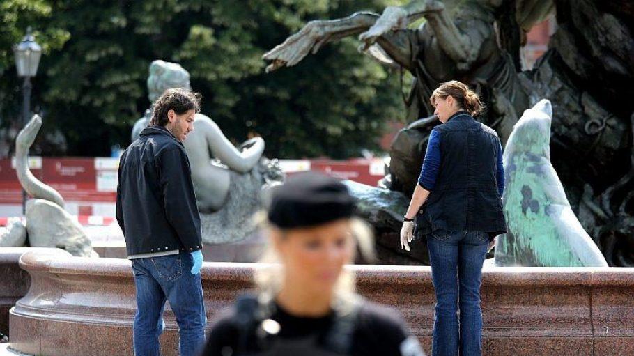 Polizisten suchen den Neptunbrunnen nach Spuren des tragischen Geschehens ab.